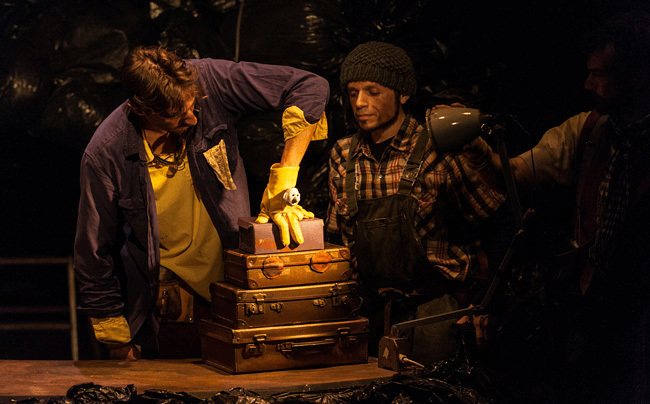 A yellow glove with a little face sits on top of a pile of old leather suitcases. A performer's hand is in the glove, to create the body and a light is shining on the puppet