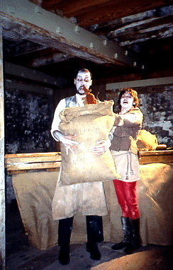 a millworker holds a large bag of flour with a puppet rat peaking out of the bag, as another millworkers watches