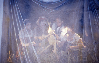 4 performers manipulate a puppet boy made out of straw, behind a clear silk cloth