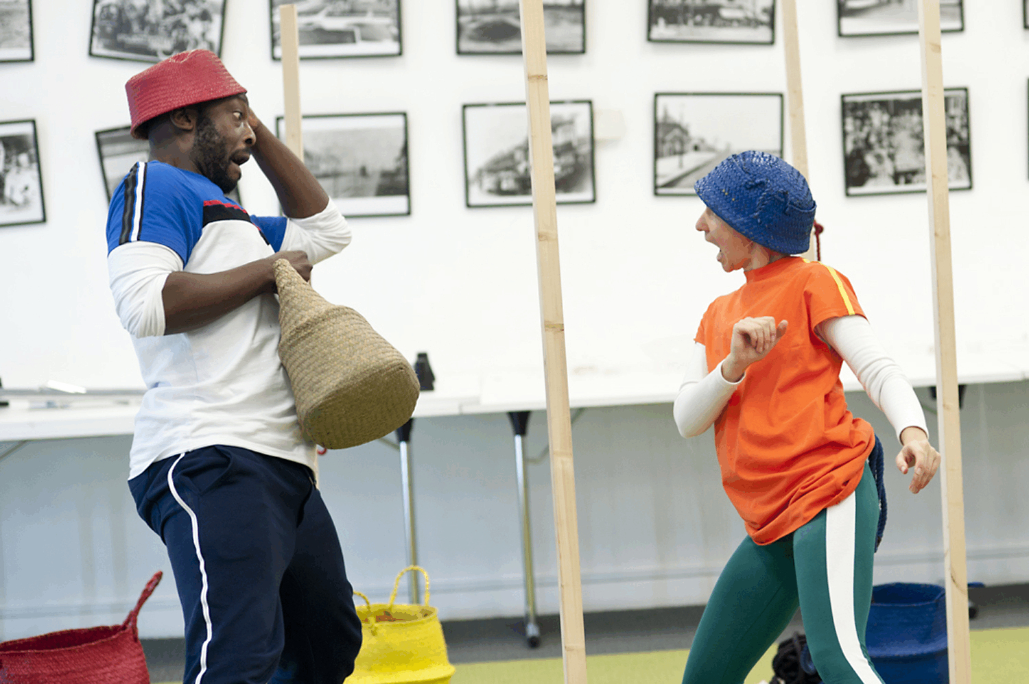one male performer with a red hat and basket being little red riding hood meets one female performer wearing a blue hat with ears who is being a wolf.  They are tilting backwards