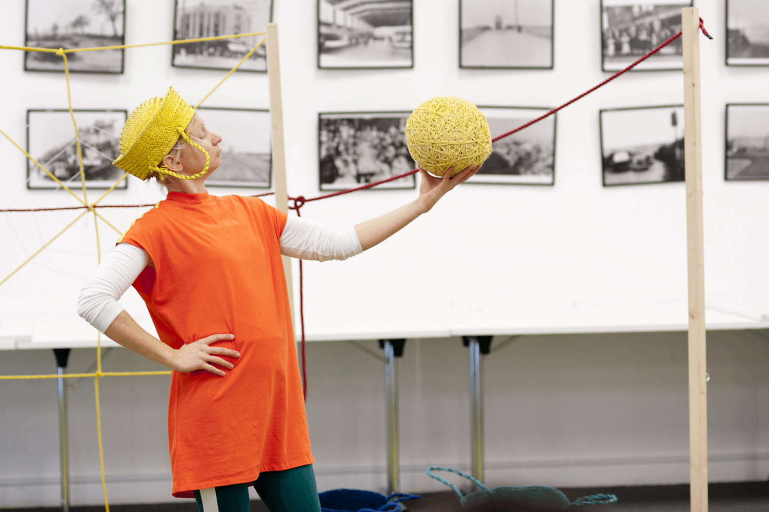 a female performer, hand on hip and wearing a yellow basket as a crown, holds a huge ball of yellow wool in the air