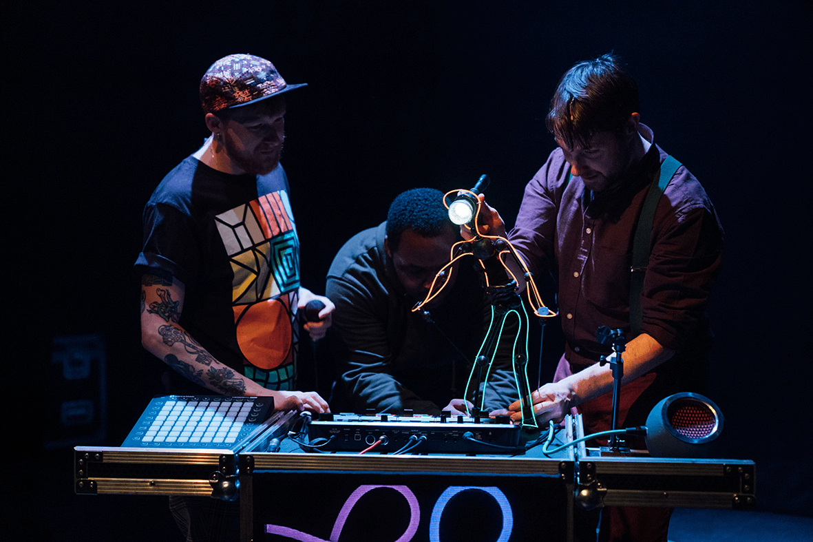Beatboxer at his music station with 2 puppeteers animating a tiny man made out of wirelight and a microphone for his head