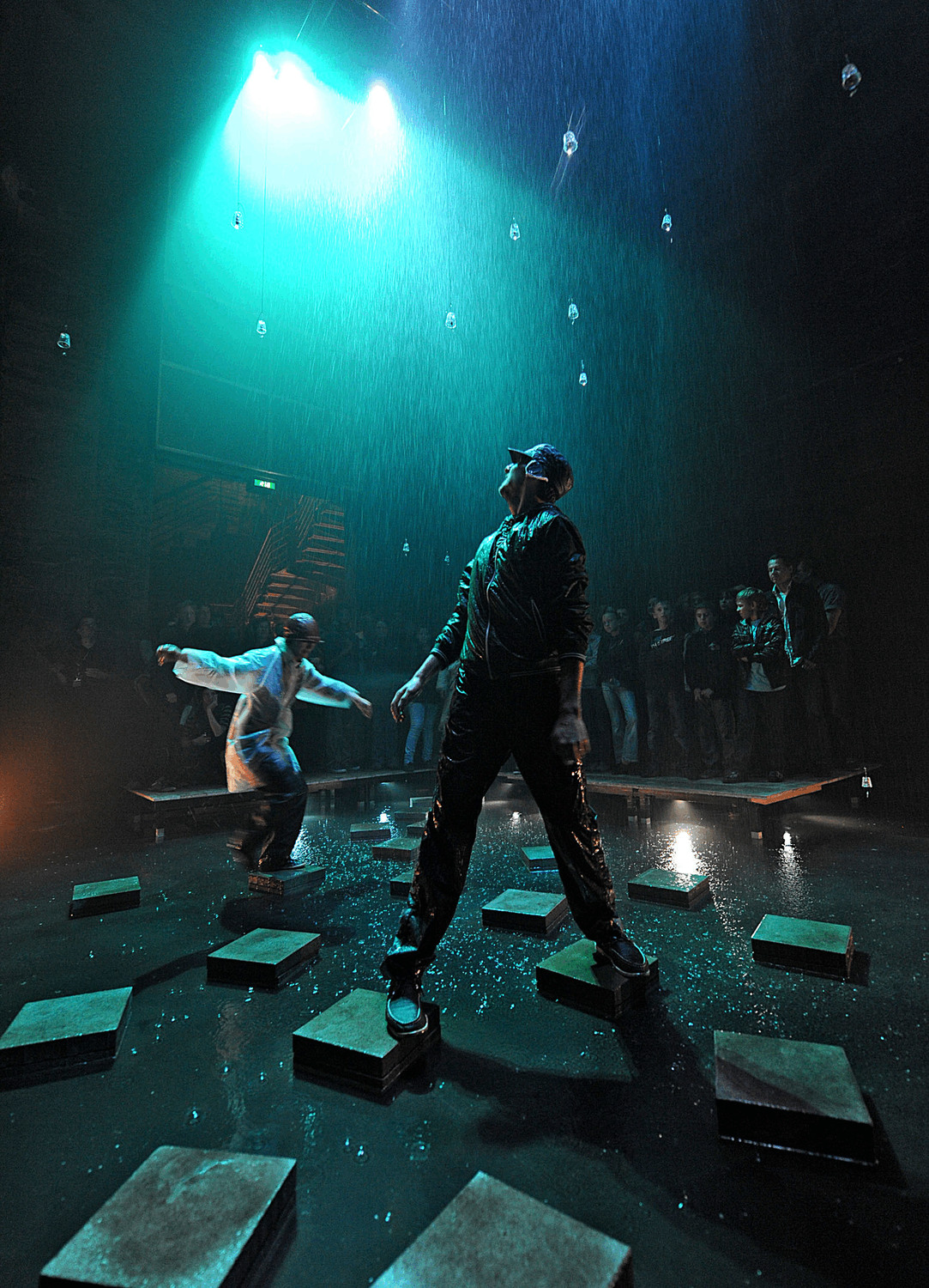 Two performers jump across water using stepping stones in a room where rain falls down upon them.