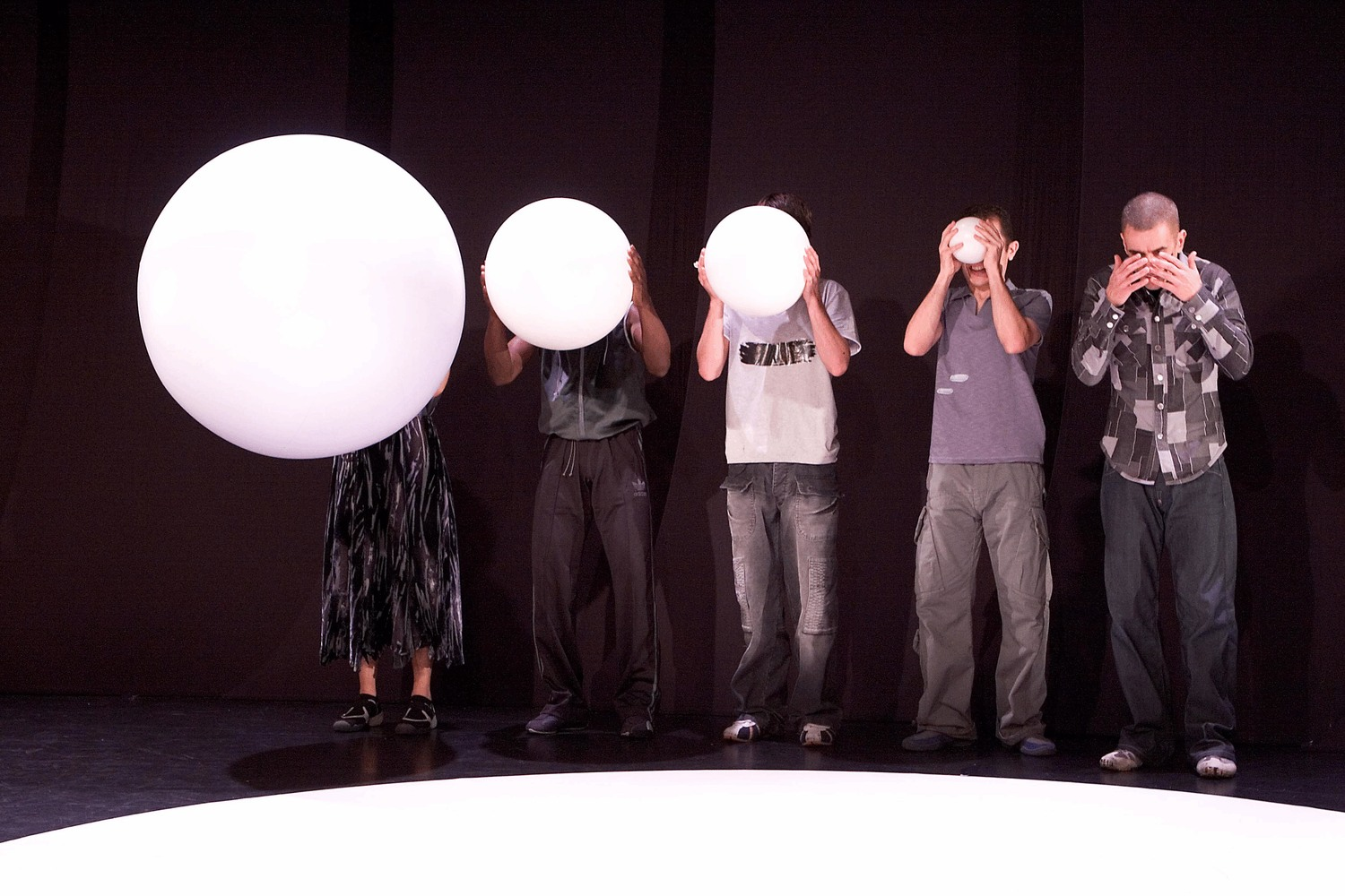 Five friends stand on the edge of a circle. The man on the right holds his hands over his eyes and the remaining four hold white balls which gradually increase in size