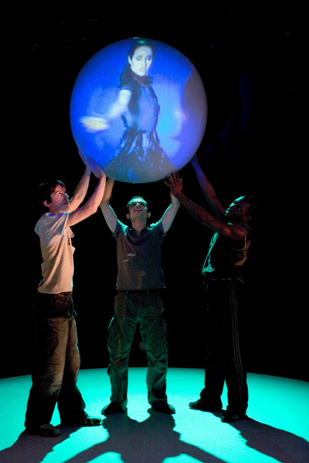 Three men standing on a glowing green circle hold a ball high in the air and inside a woman dances