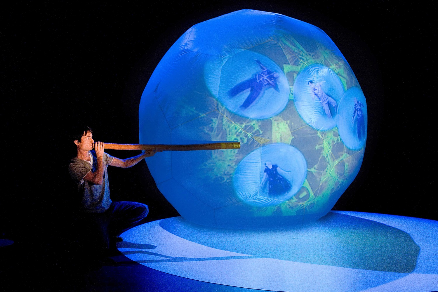 A man in shadow, standing on a glowing blue floor,  plays a diggeridoo in front of a giant ball filled with four tumbling performers spiralling in mid air.