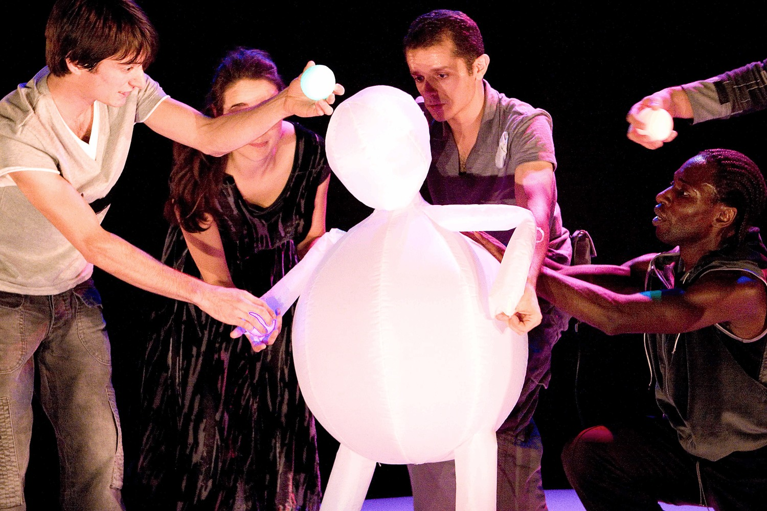 Four performers manipulate the movements of a boy made out of white balloons, trying to encourage him to play a ball game