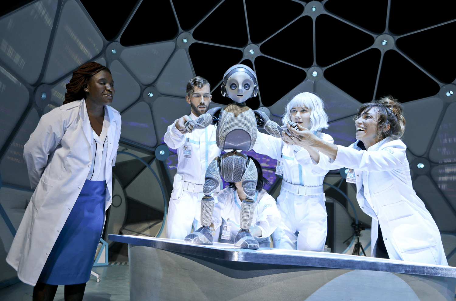 Robot Boy held by 3 technicians tentatively takes his first steps inside a sci fi laboratory