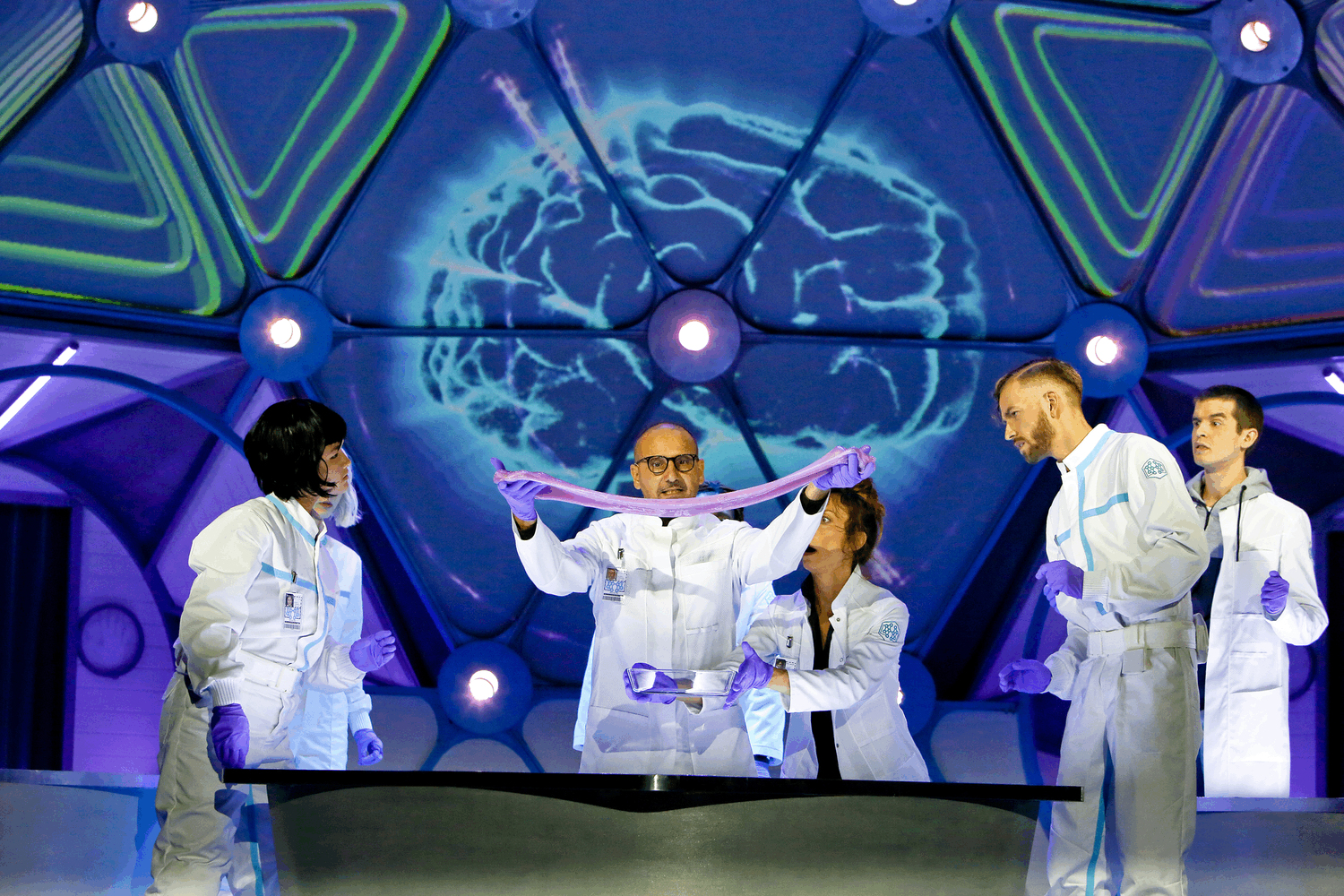 a scientist in a white coat pulls a purple slime between his two hands.  The purple slime is like the inside of a brain