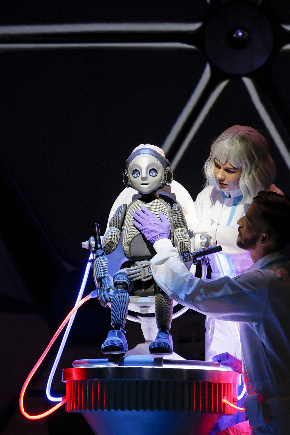 Robot Boy sitting in a chair with wires attached to him as 2 technicians check that he is OK