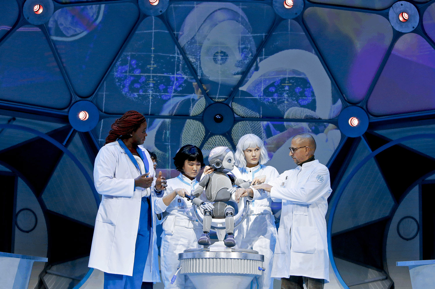 Small Robot Boy sitting in a chair surrounded by a team of Scientists.  The Robot's face is being projected onto walls behind.