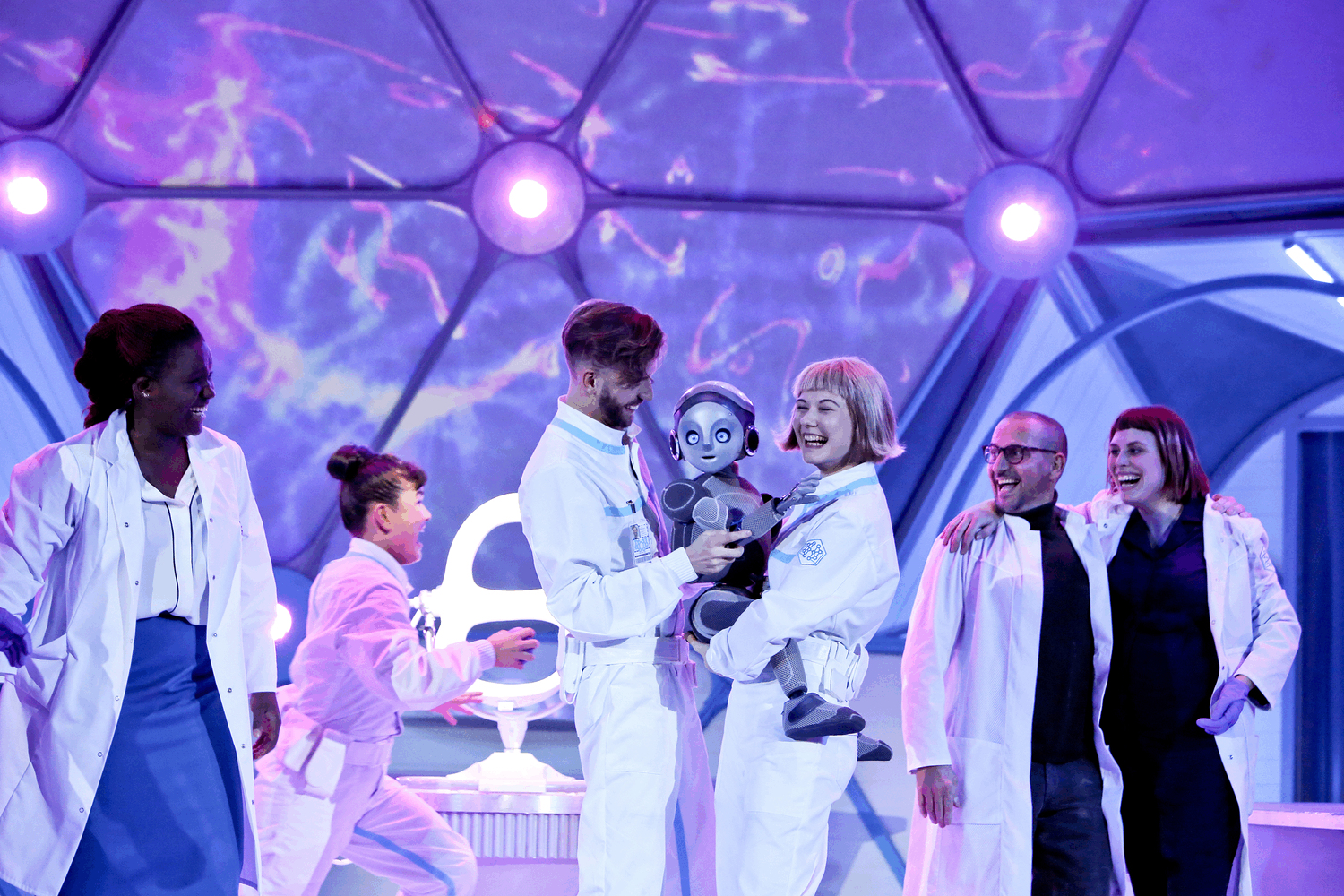 Two laboratory technicians (puppeteers) hold Robot Boy tightly as 4 scientists celebrate that Robot Boy is alive