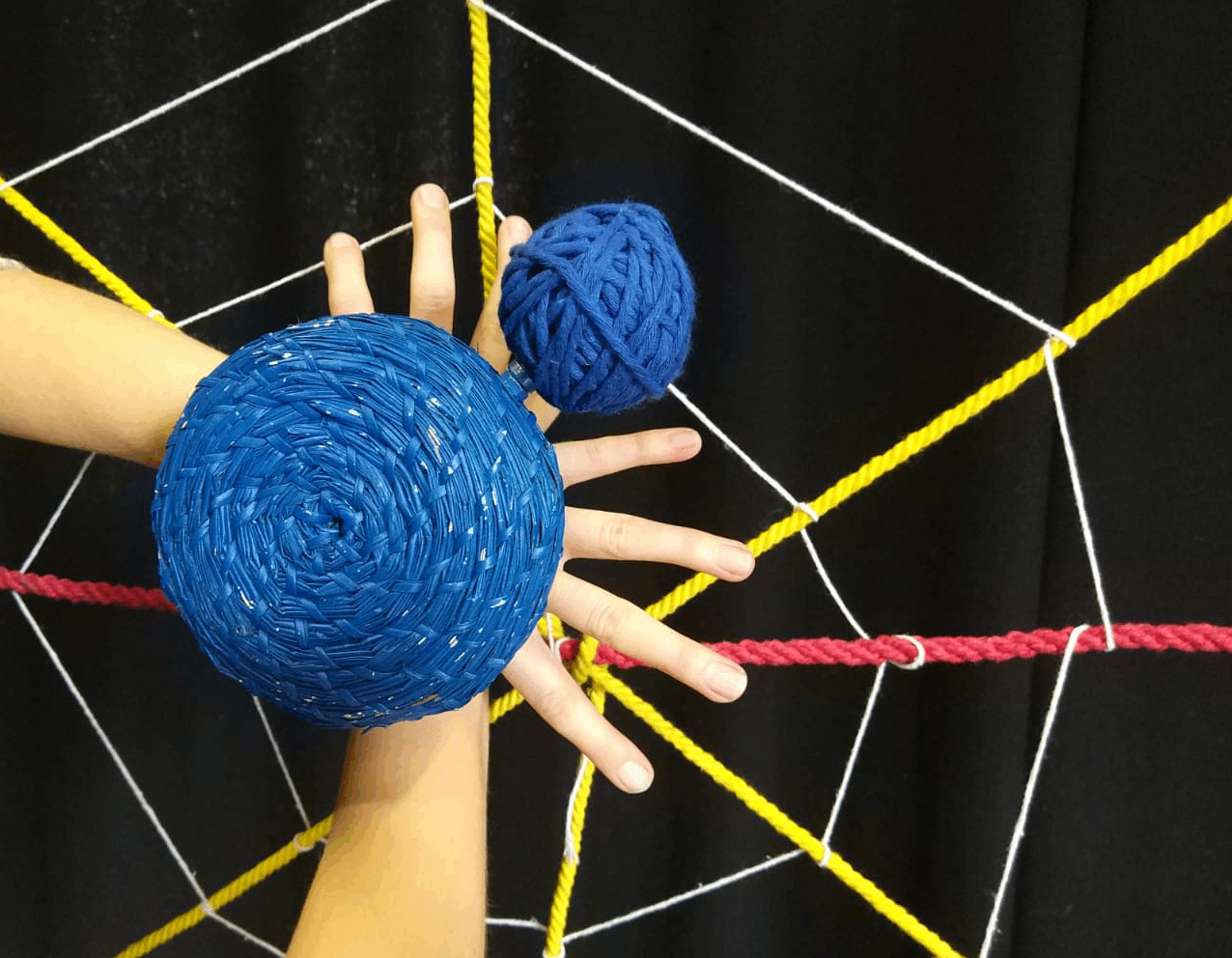 a spider's web made out of wool and string and a large blue spider made out of two hands with fingers splayed and blue baskets