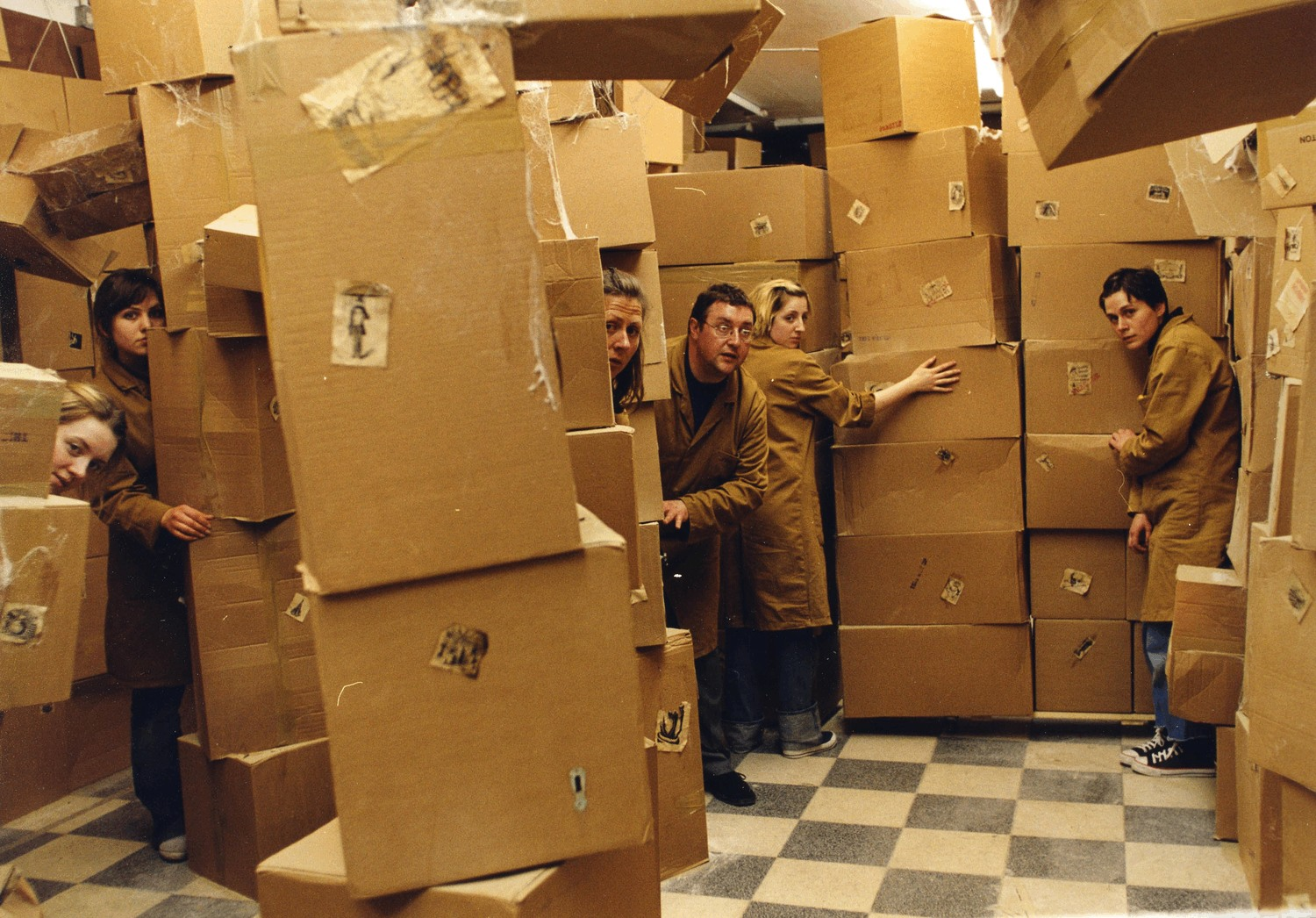 5 shopkeepers creep through a room full of towers of cardboard boxes