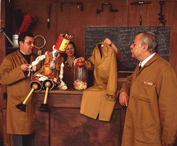 3 shopkeepers stand by a puppet boy made out of cans and objects sold in the shop, who is takling to a puppet made out of a shopkeepers coat