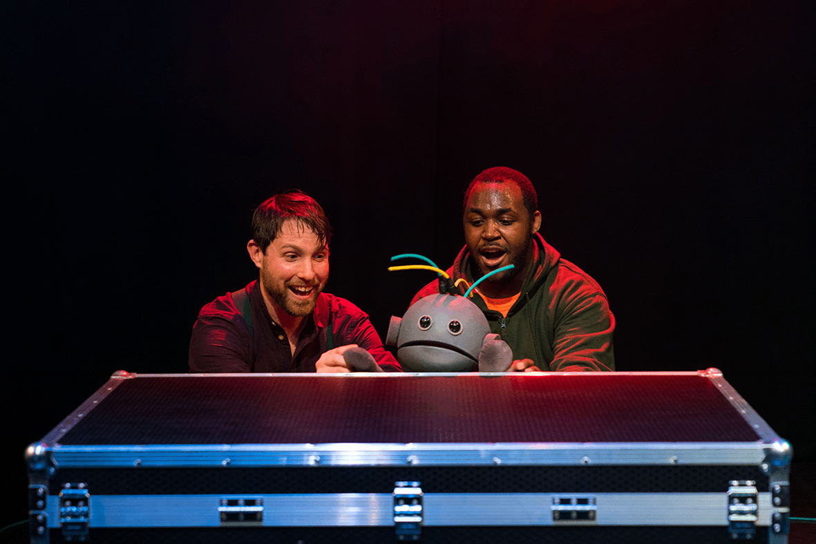 two puppeteers crouching behind a freight case, with the head of a toddler puppet peaking up from behind the case