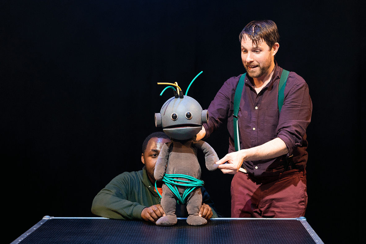 two puppeteers holding and animating a alien looking toddler puppet