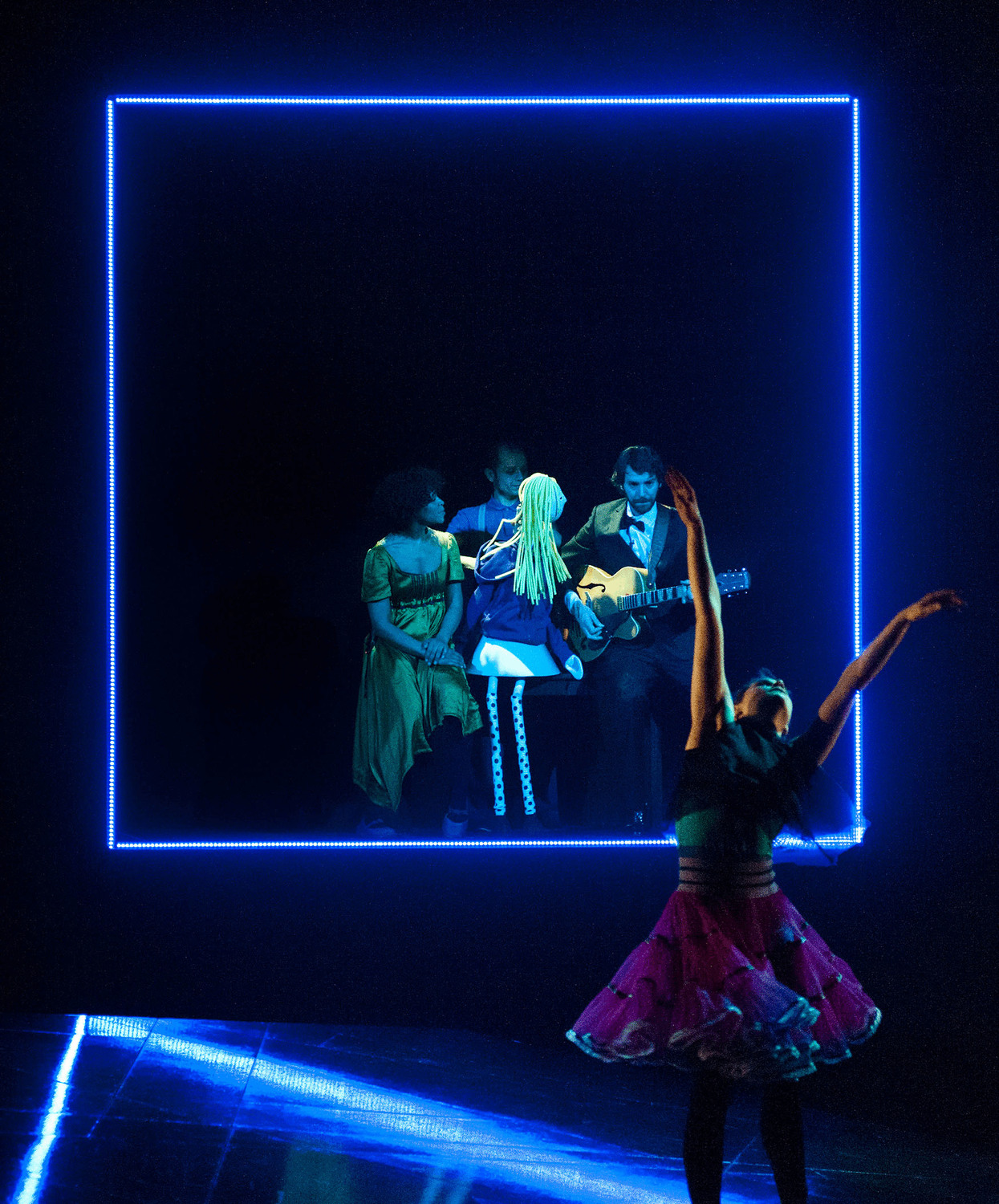 In a blue box frame at the back of the photo a teenage puppet girl sits with a guitarist and 2 performers, in the foreground a dancer moves to the music