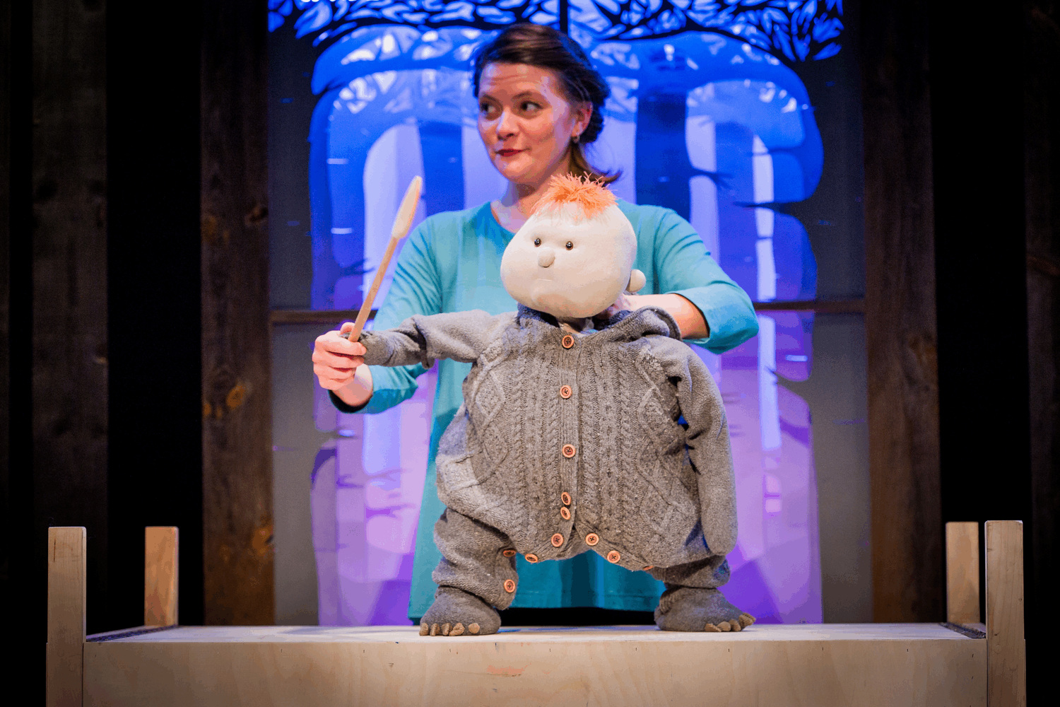 a puppeteer controls a puppet of a child, wearing a knitted baby grow, holds a wooden spoon as though conducting.