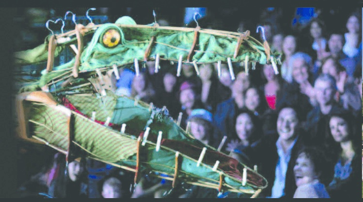 a large open crocodiles mouth is at the front of the image, made out of fabric, coat hangers and clothes pegs.  The audience can be seen in the background.