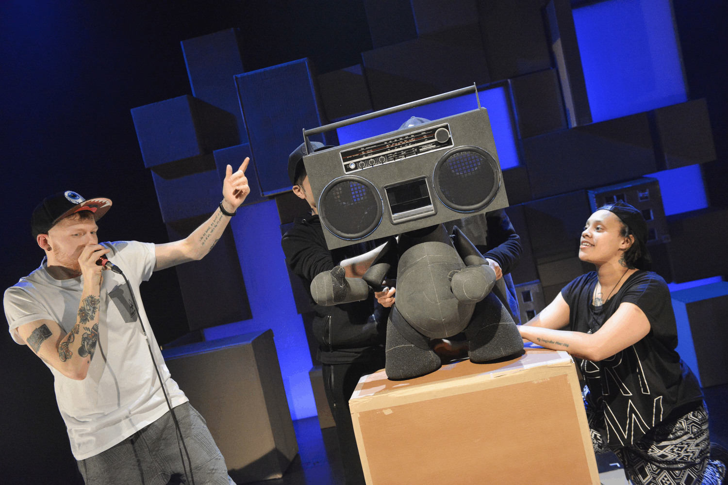 A puppet with a boom box for a head and a dummy toy body stands on a box. He is manipulated by three performers. One other performer is jamming with him.