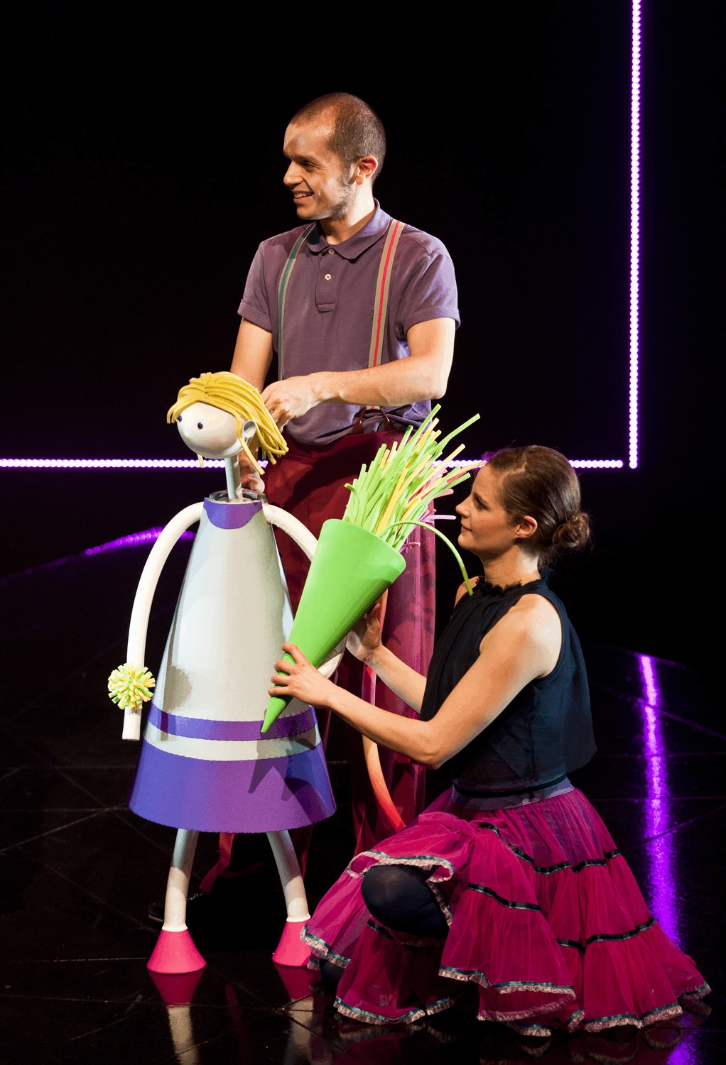 Two puppeteers control a puppet of a young girl holding a bunch of flowers