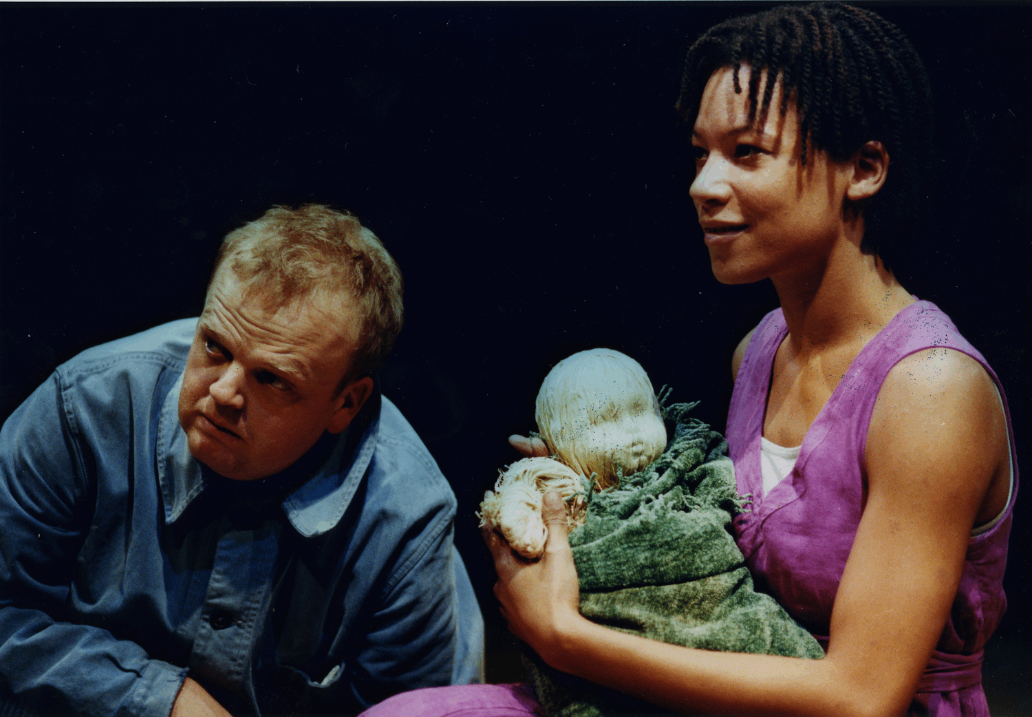 Rehearsal image of actor Toby Jones on the left and actress Nina Sosanya holding a wooden baby puppet