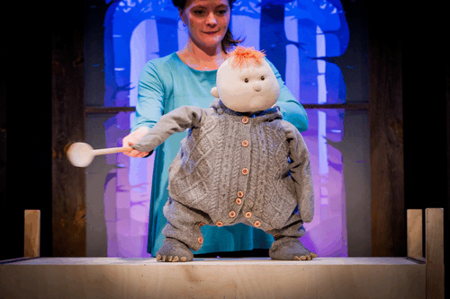 a puppet of a child in a onesie is holding a wooden spoon and looking out to the audience