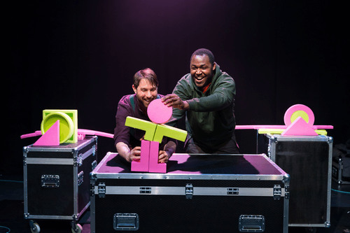 two smiling puppeteers create the shape of a person using foam shapes