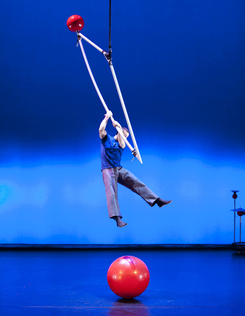an aerialist hangs in the air on to a triangular metal object as his feet try and touch a large red ball on the floor