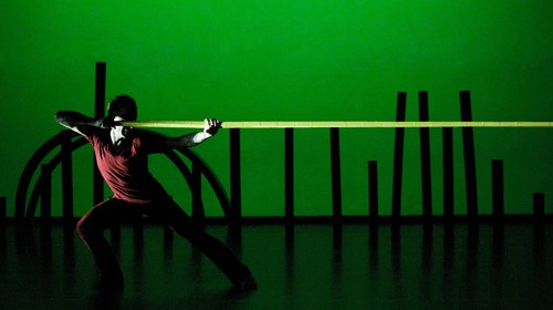 a male dancer pulls a long yellow foam line at shoulder height, across the stage against a green backdrop