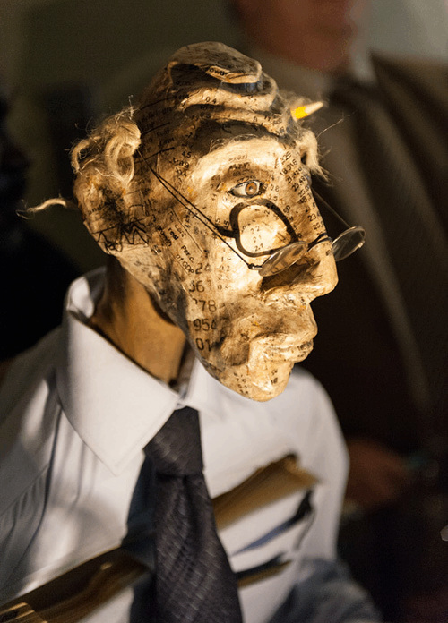 A puppet's head made out of old newspapers, shaped to look like a highcheekboned old man with waspy hair, wearing glasses and a suit and tie.