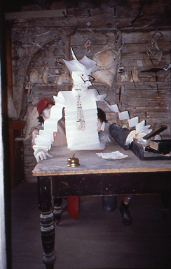 puppet made out of folded white paper, with a paper tie and glasses sitting at a desk writing