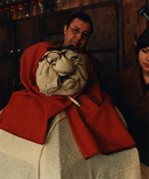 a large female puppet made out of old cloth and sack, with a large button nose, glasses and heavy eyebrows