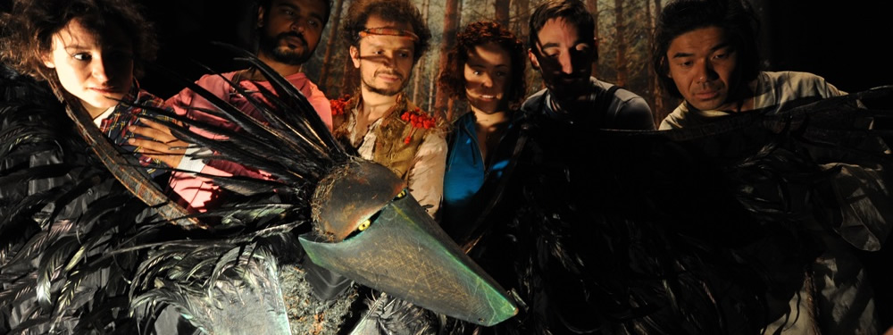 5 performers hold a giant puppet bird in a dark forest