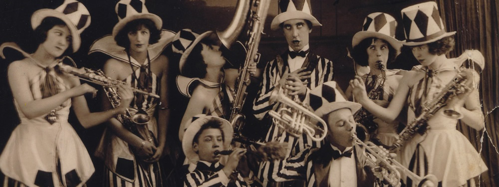 A photograph from the 1930s of a musical troupe playing  trumpets, trombones and saxaphones