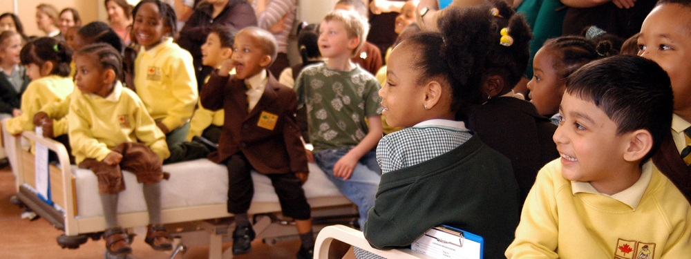 6 year old school children sit on hospital beds as they are pushed through an interactive experience in a hospital ward