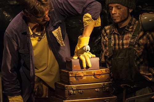 A puppeteer with his hand in a beautiful yellow glove which has a face on it, sitting on top of a tower of suitcases.