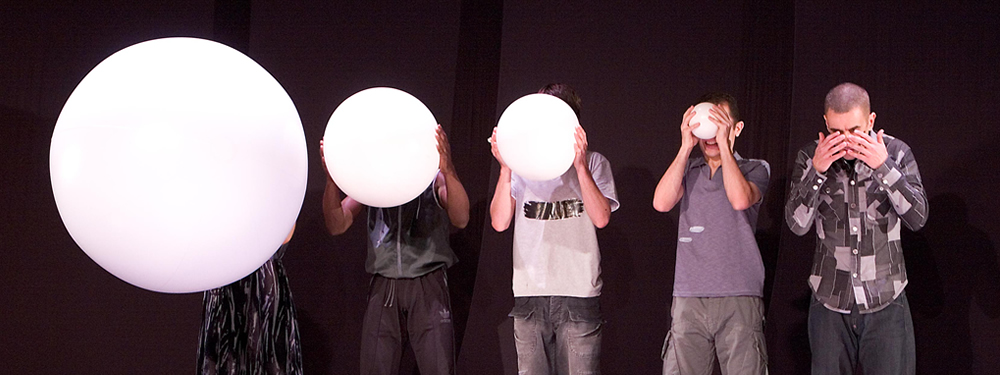 5 performers stand in a row, their faces covered by balls which become increasingly bigger